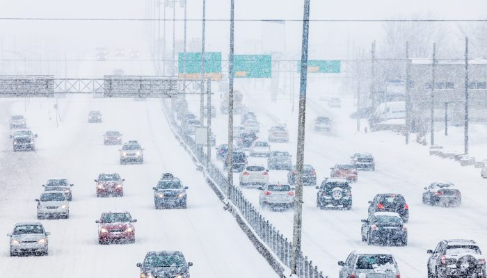 Cars driving on a snowy highway.